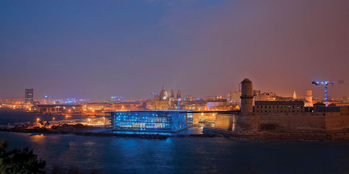 מראה כללי של הבניין בלילה על רקע העיר מרסיי