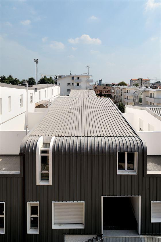 """הפרויקט משחק על השילוב בין הטקסטורה והצבע של שני אלמנטים מרכזיים: מעטה אפור ביריעת פלדה מגלוונת עם טקסטורה אנכית שמצפה ללא הפרעה את החזית הצפונית והדרומית ואת הגגות, והטיוח של ההגבהה המזרחית והמערבית. הקומפלקס כולל 37 דירות, עם שטחי דירה שנעים בין שטח מינימאלי של 42 מ""""ר ועד שטח מקסימלי של 93 מ""""ר."""