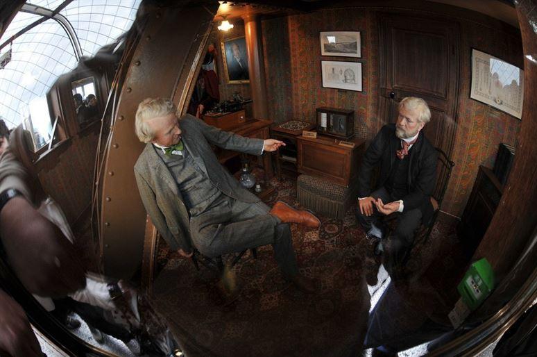 גוסטב אייפל ותומס אדיסון, מתרועעים בחדרו הניסתר והיוקרתי של אייפל, בראש מגדל אייפל (הנצחה בשעווה).