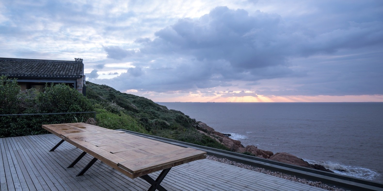 the-wooden-rooftop-deck-is-edged-with-river-stone