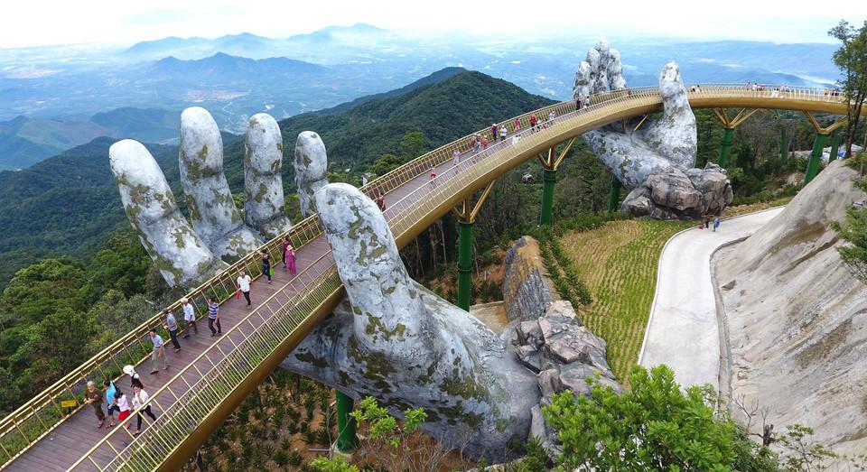 זוג ידיים ענקיות מרימות את גשר דה נאנג המוזהב של ויטנאם אל השמים