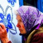 סבתא צ'כית בת 93, מעטרת בפרחים מצוירים את בתי שכניה בכפר